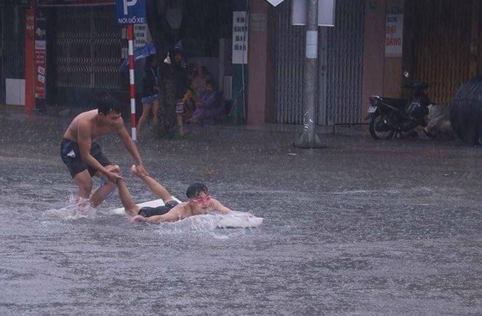 Các bạn trẻ nô đùa trong nước trên đường phố